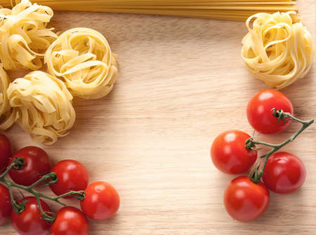 Ripe red cherry tomatoes, spaghetti and pasta strips for tagliatelle or fettuccini with central copyspace Stock Photo