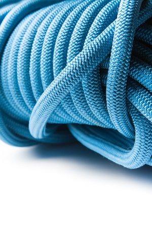 Closeup of a roll of blue rope showing the pattern created by the interwoven fibres giving the rope its strength and durability
