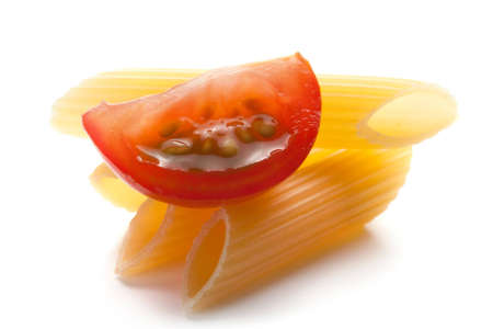 Raw tubular penne pasta and sliced ripe tomato used as ingredients in Italian cusine photo