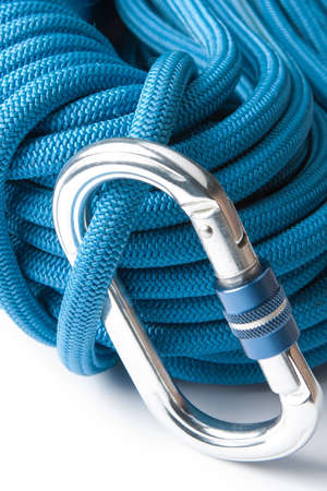 karabiner: Close up of mountaineering equipment with a blue plaited polyester climbing rope with an aluminium screw gate karabiner