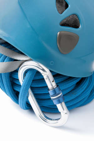 karabiner: Mountaineering safety equipment with a rolled blue braided polyester climbing rope, safety helmet and aluminium karabiner or connecting clip Stock Photo