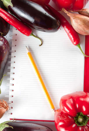 Open blank ringbound notebook surrounded by a variety of fresh vegetables for your shopping or grocery list Stock Photo