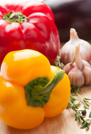 Colourful red and orange bell peppers with garlic and herbs to be used as ingredients in cooking Stock Photo