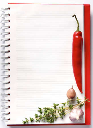 Open blank ringbound notebook surrounded by a fresh vegetables and spice for your shopping or grocery list