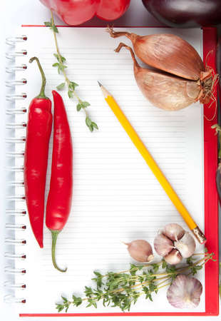 Blank lined notepad with a pencil and fresh ingredients including thyme, onion, garlic and chili peppers for your recipe or cooking tips photo