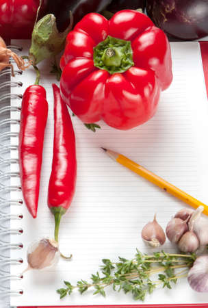 Blank lined notepad with a pencil and fresh ingredients including thyme, garlic and chili peppers for your recipe or cooking tips photo