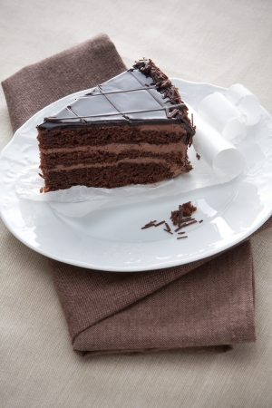 Slice of gourmet layered chocolate cake with creamy chocolate filling and rich choclate icing served on a plain white plate for a delicious dessert photo