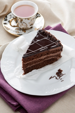 Large slice of rich delicious gourmet chocolate cake served on a plate with a dainty porclain cup of hot tea for elegant entertaining Stock Photo