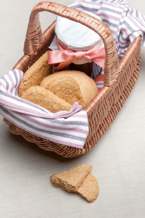 High angle view of golden crunchy oatmeal cookies and a bottle of berry jam in a wicker picnic basket for a delicious snack