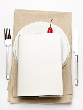 White Hardbook on top of a plate setting with knife and fork and red chili showing.