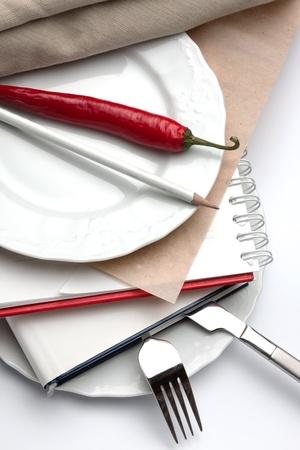 casein: Libros intercalada entre las placas blancas con un cuchillo y el tenedor en el plato de fondo, un l�piz blanco y un chile rojo en la parte superior. Foto de archivo