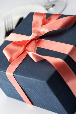 Closeup of a black gift box tied with a decorative red ribbon and bow for that special loved one to celebrate a birthday, anniversary Christmas or Valentines photo