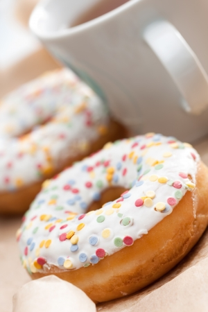 Golden freshly baked doughnut glazed with icing and sprinkles served with a mug of tea or coffee, tilted angle with shallow dof Stock Photo