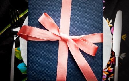 Overhead view of a gift box tied with a decorative red bow resting on a plate on a table setting