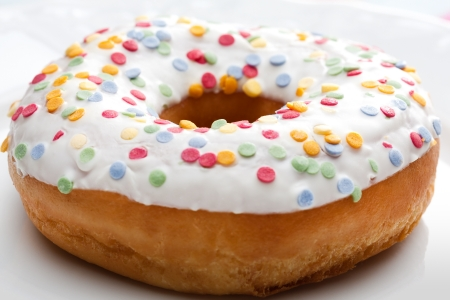 Freshly baked golden doughnut glazed with white icing and colourful sprinkles for a delicious teatime snack