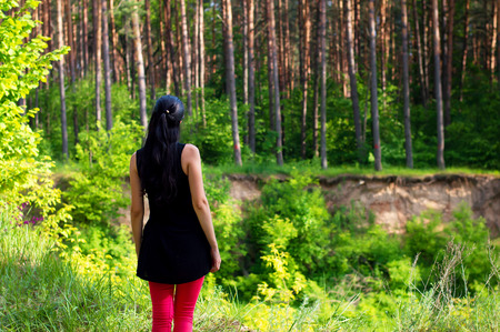 red jeans: One brunette female in red jeans and black t-shirt standing in the green forest