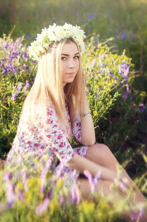 coronet: Blond girl with flower coronet sitting in the field with grass and purple flowers