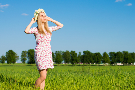 Young blond woman with long hair dressed in a dress with floral pattern standing in the green field, blue sky on the background