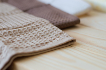 selective focus: Kitchen towels of brown color on a wooden table, selective focus