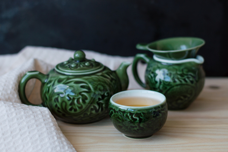 Tea set with blurred ornament of green color for traditional chinese tea ceremony