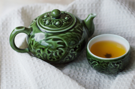 Chinese tea in a special tea bowl and tea pot on white towel Stock Photo