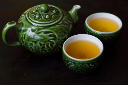 Green tea in two small cups and chinese traditional tea kettle Stock Photo