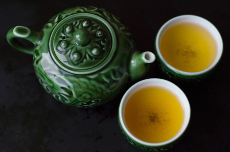 chinese tea pot: Two cups of green tea and traditional chinese tea pot for tea ceremony, view from above
