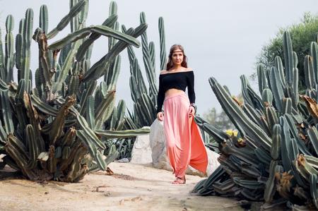 mujer hippie: hippie de la mujer en la falda larga de color rosa a pie cerca de las grandes cactus Foto de archivo