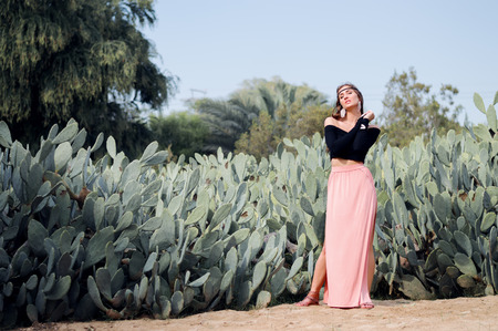 hippie woman: Young hippie woman in long pink skirt standing near field of cactuses