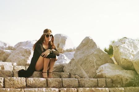 mujer hippie: hippie de la mujer joven que se sienta en las escaleras cerca de las piedras grandes