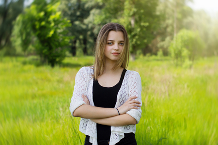 Portrait of a female teenager standing in the park Stock Photo