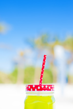 red straw: Vertical photo of juice in a glass with a red straw, sky as background