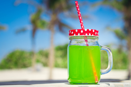 red straw: Juice of bright green color in a glass with a red straw Stock Photo