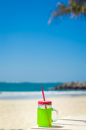 red straw: Vertical photo of green juice in a funny glass with a red straw, beach as background