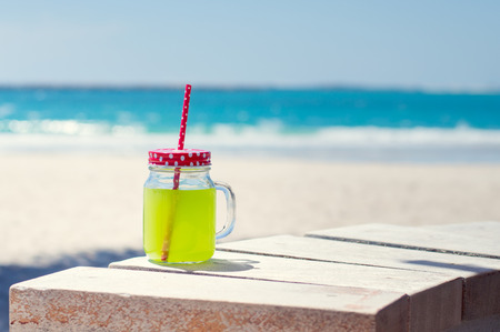 red straw: Glass of green juice near seaside line Stock Photo