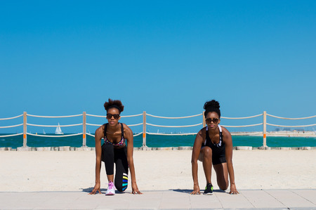 Two african females in sportswear and with sport hairstyle doing exercises in front of the sea at Dubai beach in the UAE Stock Photo