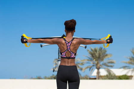 One female athlete of african ethnicity doing exercises with ropes for suspension training. Outdoor sport activity concept