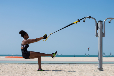 Young woman of african ethnicity balancing using special ropes for suspension training. Outdoor sport activity concept