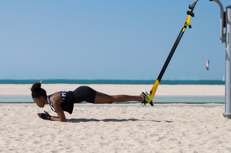 Female african doing difficult exercises using special ropes for suspension training. Sport activity at the beach in Dubai, UAE Stock Photo