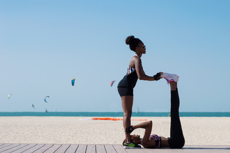 Two female african athlete exercise at Dubai beach in the UAE. Two young women workout near seaside