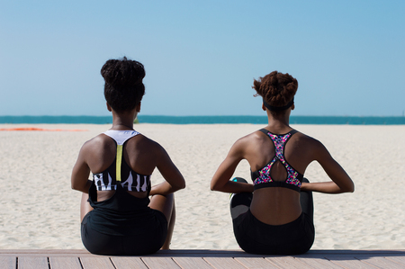 Two african females sitting on wooden platform at Dubai beach. Young african women have a break near seaside line after intense outdoor workout Stock Photo