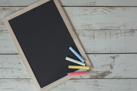 Clean and empty framed blackboard with colorful chalks on wooden background. Chalkboard on gray table. Back to school concept