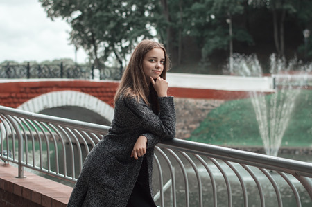 Positive female teenager standing near bridge un the park. Autumn season. Young female in grey knitted coat, handmade outfit Stock Photo
