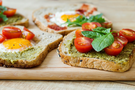 Breakfast toasts with multicereal bread, pesto sauce, cherry tomatoes, eggs, spinach on wooden cutting board. Healthy breakfast. Balanced meal  Stock Photo