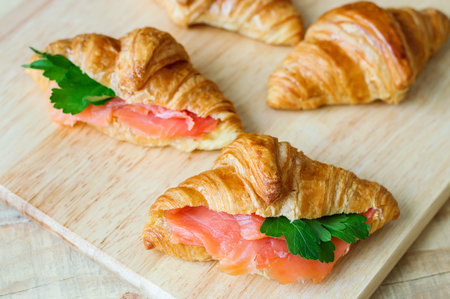 Croissant sandwiches with salmon and green parsley. Croissants with red fish on wooden cutting board. Healthy breakfast. Appetizer. Starter meal Stock Photo