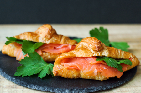 Breakfast sandwiches with mini croissants, smoked salmon slices and parsley on black slate board. Croissants with red fish and herbs. Breakfast meal