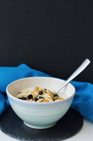 Porridge with oats, milk, banana slices, raisin and nuts served in a blue bowl with spoon on black slate board with blue napkin. Vertical photo. Healthy eating concept. Breakfast meal