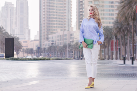 Young european woman with curly blond hair and trendy make up standing near empty road in Dubai downtown, UAE. Stylish business woman in blue blouse, white trousers, yellow shoes and green handbag Banco de Imagens