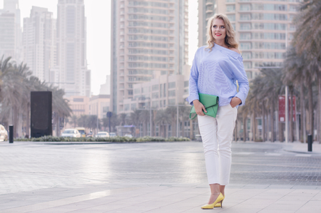 Smiling european female with blond hair standing near empty road in Dubai, UAE. Young business woman with green bag and in yellow shoes with high heels