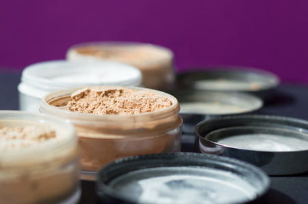 Mineral make up powder for matt skin. Variety of containers with beige and white powder for facial care. Focus on beige powder, purple background Reklamní fotografie - 94810698